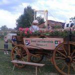 Mitglieder des Vereins stehen vor einem geschmückten historischen Wagen