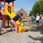 Kinder rutschen eine gelbe Rutsche herunter.