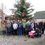 eine große Wandergruppe steht vor einem geschmückten Tannenbaum auf einem Dorfplatz.
