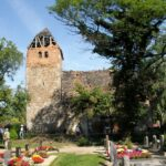 Großaufnahme der teilweise zerfallenen Kirche in Schrenz mit Friedhof im Vordergrund