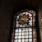 Großaufnahme: Teilweise kaputtes Kirchenfenster mit Bemalung