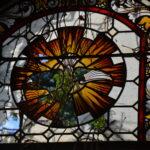 Nahaufnahme: Teilweise kaputtes Kirchenfenster mit Bemalung