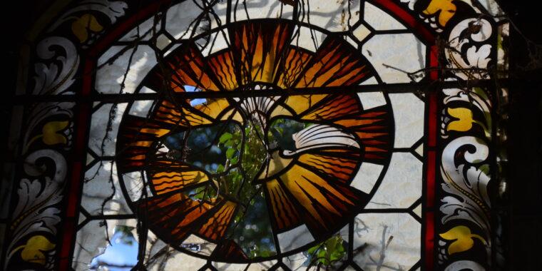 Nahaufnahme eines teilweise kaputten Kirchenfensters mit Bemalung