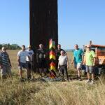 Gruppe von Männern neben einer kleinen schwarz-rot-gelben Grenzsäule