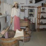 Historische Waschküche mit verschiedenen Geräten und einer Kleiderpuppe