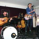 Blues-Performer Abi Wallenstein und Rudy Wittenberg mit Gitarren auf einer kleinen Bühne