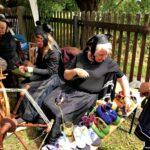 3 Frauen in schwarzen Gewänden und schwarzen Hüten, die an alten Spinnrädern arbeiten