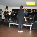 Gruppe Jugendlicher an verschiedenen Instrumenten auf einer kleinen Bühne
