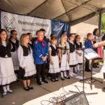 Eine Gruppe kleiner Mädchen und Jungen singen auf einer kleinen Bühne mit Akkordionbegleitung