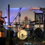 Band aus 4 Männern an Gitarre, Bass, Schlagzeug und Mikrofon auf einer kleinen Bühne in gemütlicher Atmosphäre